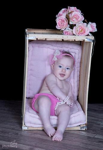 תינוקת יושבת בארגז עם פרחים