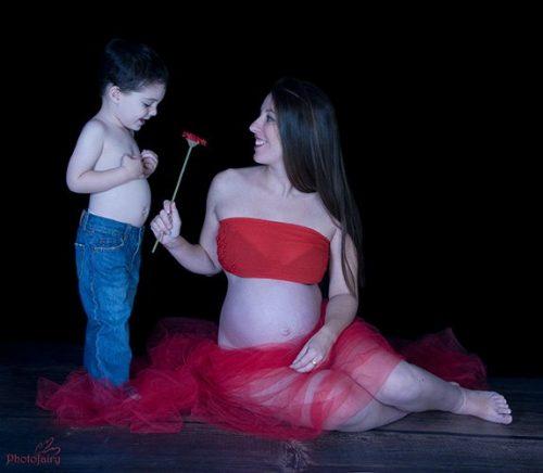 תמונת היריון בשילוב ילדים- ילד נותן לאמא פרח
