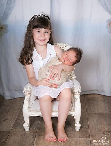צילומי ניו בורן בסטודיו- אחות מחבקת את האח חדש