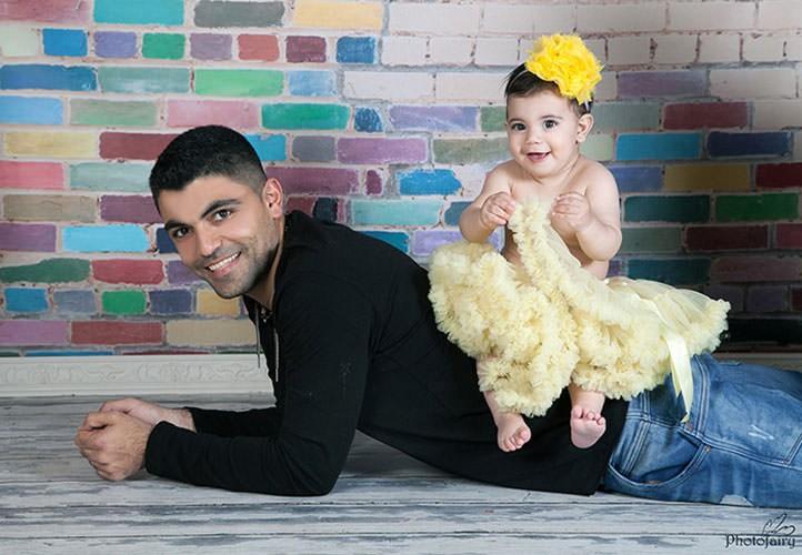 תינוקת יושבת על אבא בתמונה משגעת