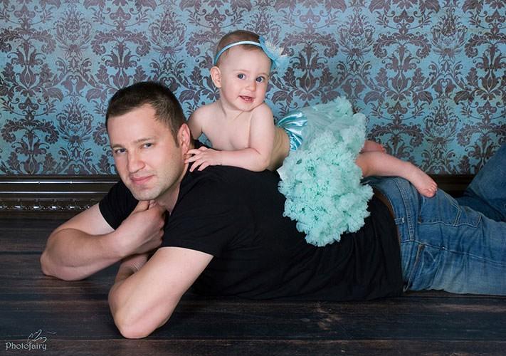אבא ובת- תינוקת מתוקה שוכבת על הגב של אבא