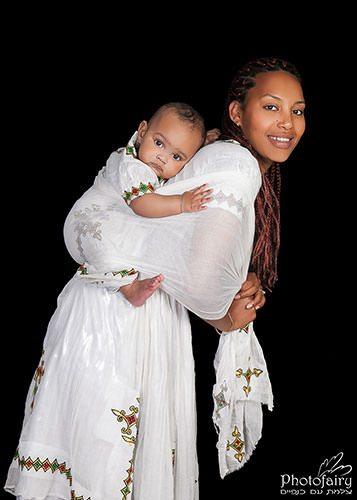 צילומי משפחה-אמא ותינוקת קשורה על הגב בבגד אתיופי מסורתי