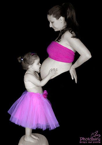 צילום הריון עם ילדים- ילדה מנשקת את הבטן של אמא