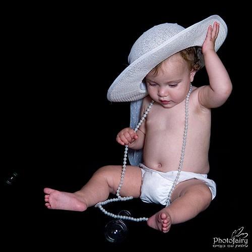 תינוקת עם שרשרת פנינים וכובע לבן מקסים