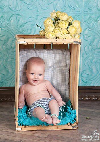 צילום מקצועי לתינוק יושב בארגז