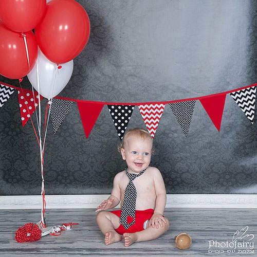 תינוק עם בלונים אדומים