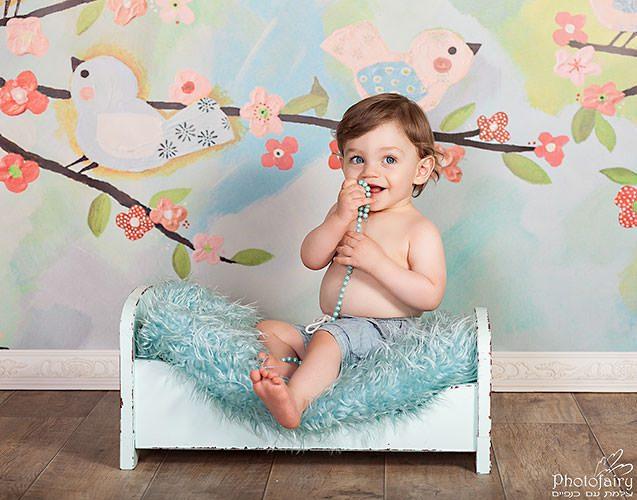 צילום תינוק בצבעי תכלת וירקרק עם ציפורים