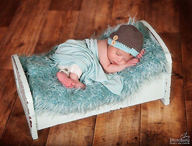 צילום ניובורן תינוקי ישן על מיטה בגווני ירקרק
