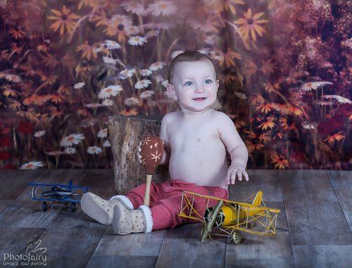 צילום תינוקות בסטודיו מקצועי - תינוק טייס עם רקע פרחים