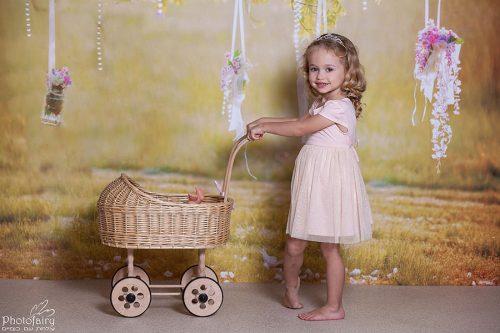 צלמת ילדים- ילדה משחקת בעגלה