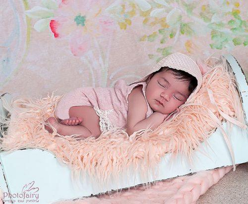 צילומי ניובורן תינוקת ישנה על מיטה בסגנון רומנטי