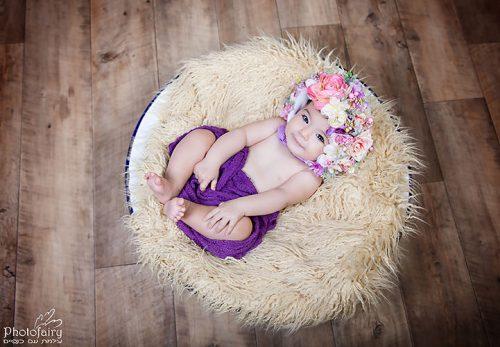 צילום תינוקות מקצועי ומסוגנן. תינוקת שוכבת בתוך קערה עם כובע פרחים