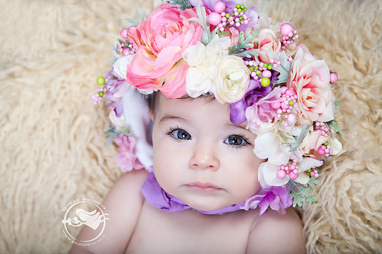צילומי תינוקות מרהיבים. תינוקת עם כובע פרחים בתקריב