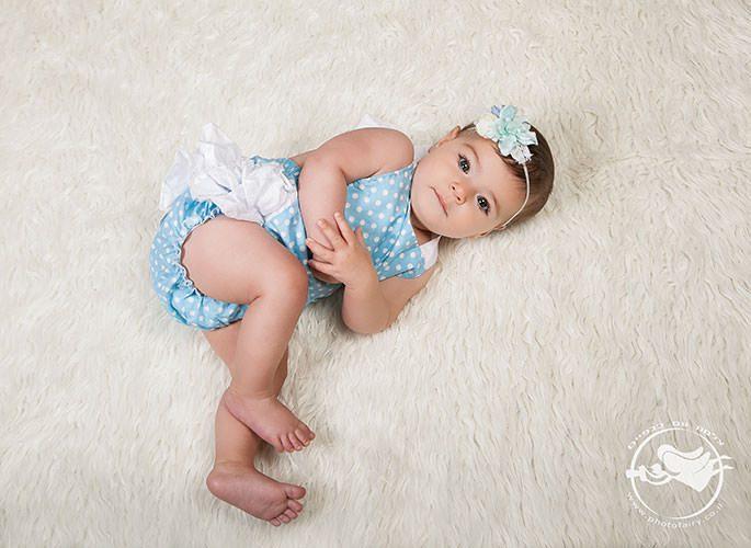 צילום תינוקות בגיל חצי שנה תינוקות שוכבת על שטיח לבן