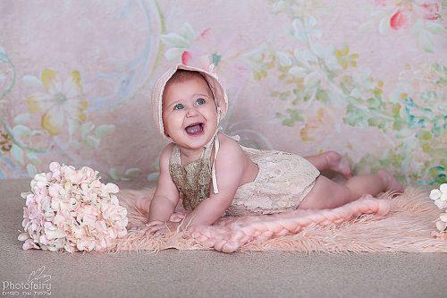 צילום תינוקת- תינוקת שוכבת על הבטן וחייכת