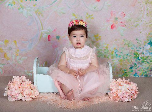צילום תינוקת יושבת על מיטונת עם פרחים