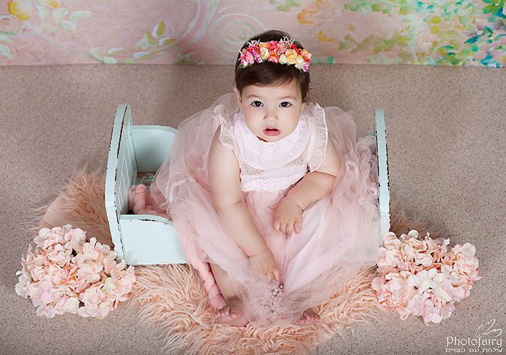 צילום תינוקות בסטודיו מאובזר תינוקת עם פרחים בסגנון רומנטי
