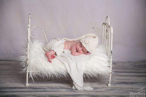 צילומי ניובורן בסגנון קלאס קסום- תינוק על מיטה לבנה