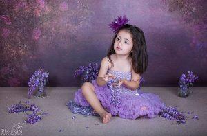 צילום ילדים -ילדה עם פרחים סגולים