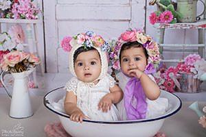 צילום תינוקות תאומות עם כובעי פרחים