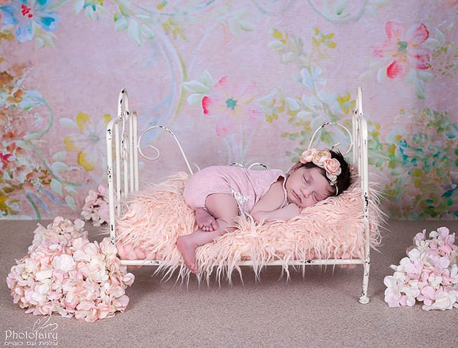 צילומי ניובורן לתינוקת על מיטה בגווני אפרסק