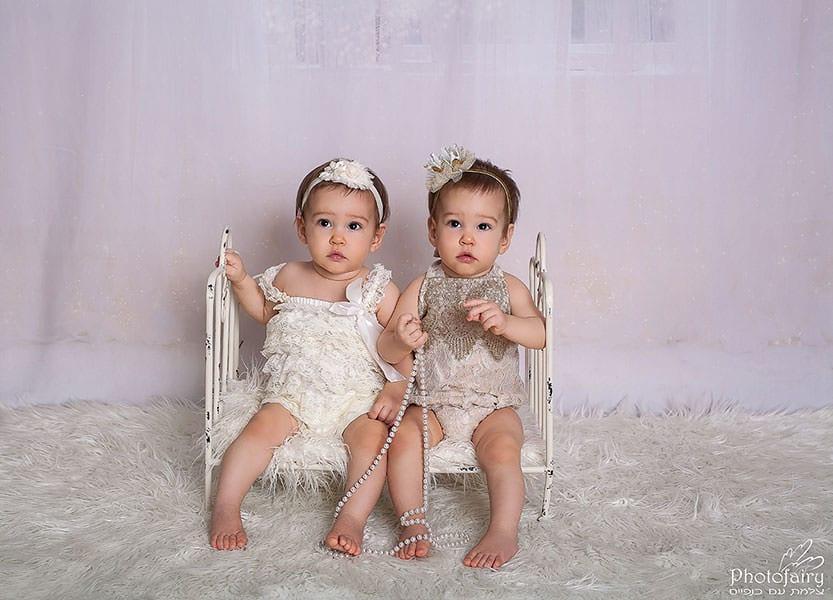 צילום תינוקות- תאומות יושבות ביחד בלבן וזהב