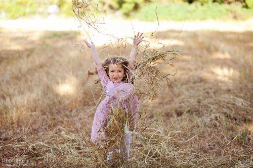 צילום ילדים- ילדה מעיפה קש באוויר