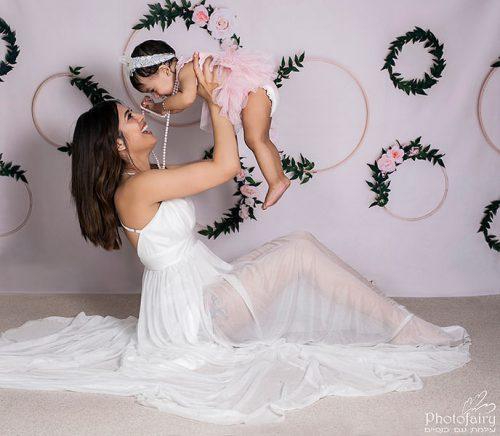 אמא מרימה את התינוקת באוויר להצחיק אותה - צילומי אמא ובייבי