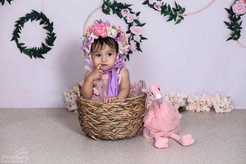תינוקת בסלסלה עם כובע פרחים משגע